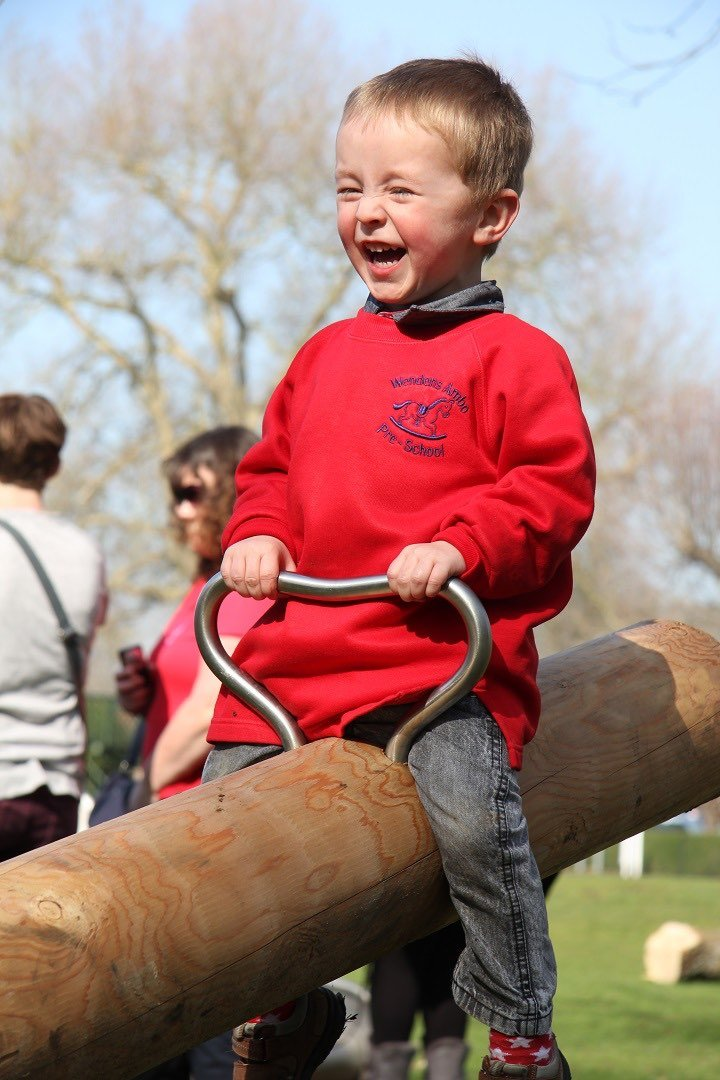 boy-smiling-while-on-the-see-saw-at-the-audley-end-miniature-railway